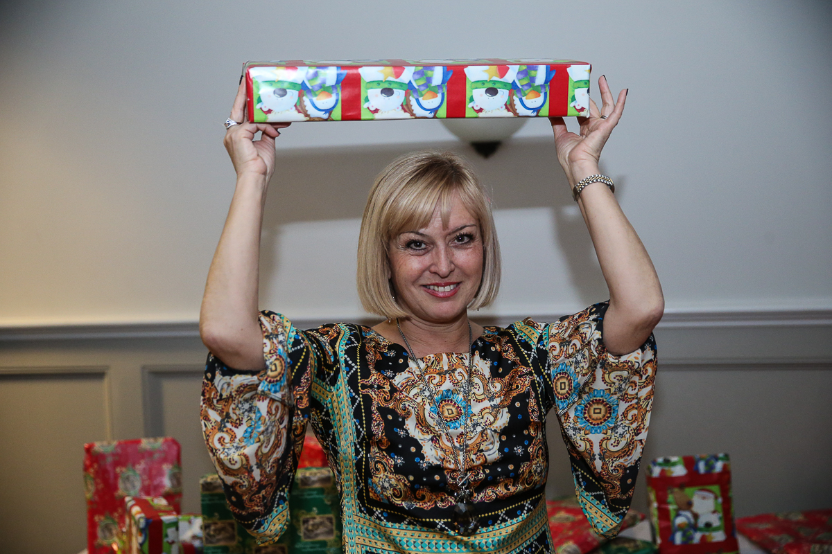 Photo By Curtis Knight.  Pretty girl holds up present at party.