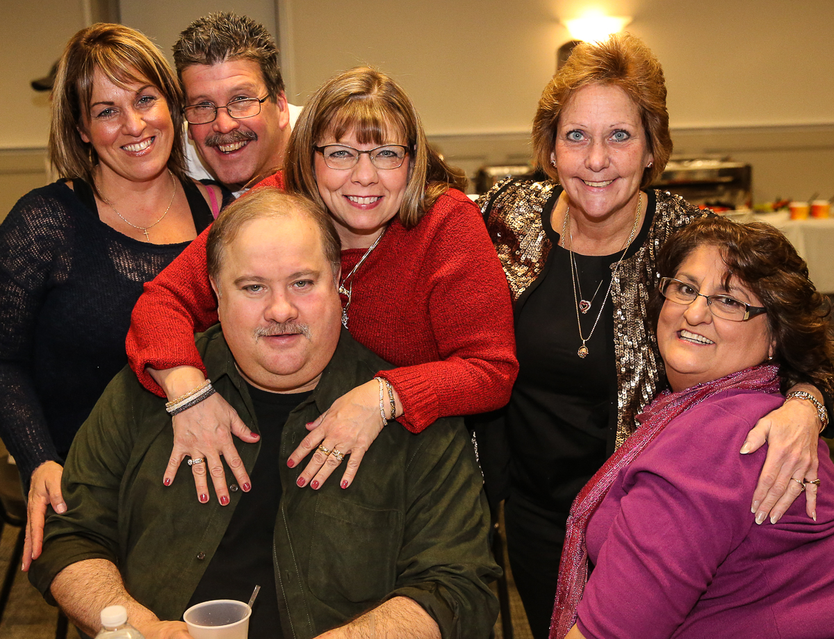 Photo By Curtis Knight.  Group shot of 6 people sitting at a table at the Lynnway auto Holiday Party.